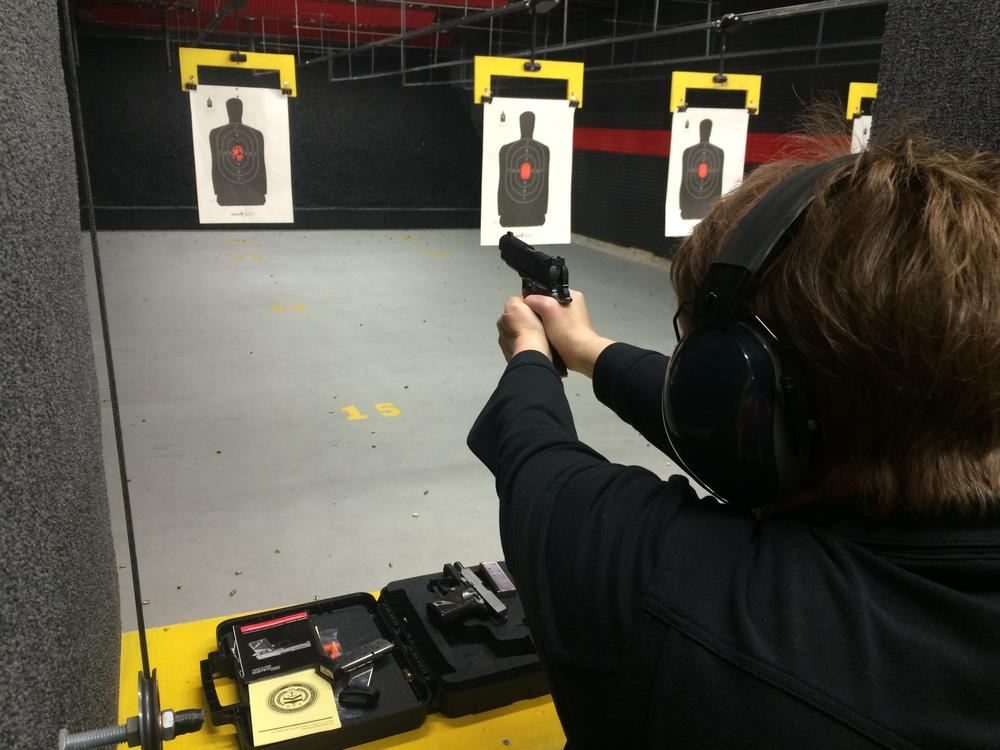person wearing a black long sleeve shirt and ear protectors shooting a pistol at a paper target