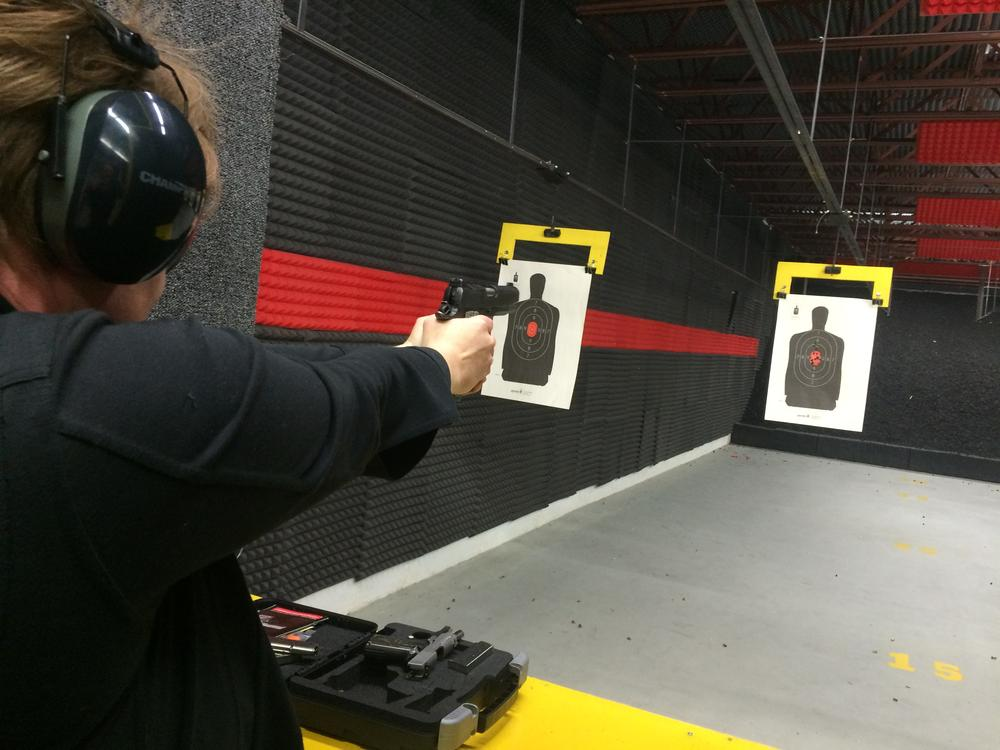 person wearing a black long sleeve shirt shooting a pistol at a paper target