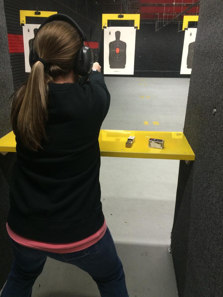 person in a long sleeve black shirt with black ear protectors looking at a paper target of a person