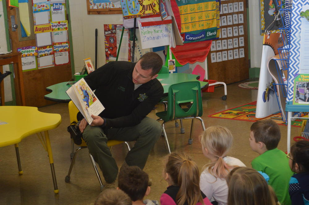 Deputy Green reading a book to kindergarten students