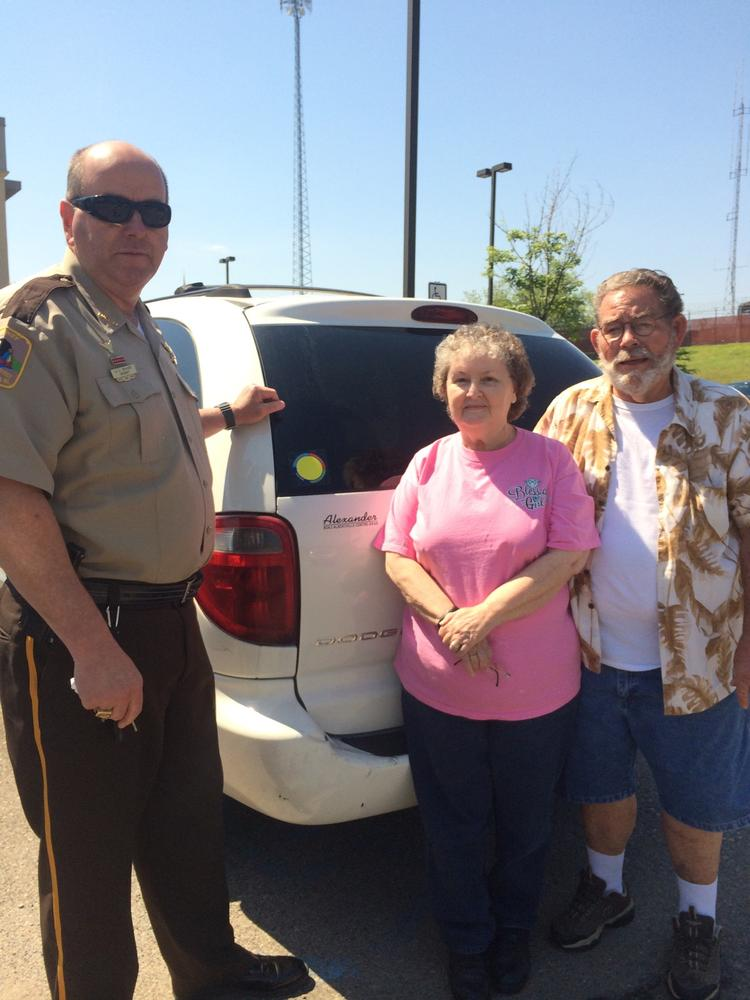 Sheriff Shaver with Larry and Joan Beck showing the yellow dot sticker on their vehicle