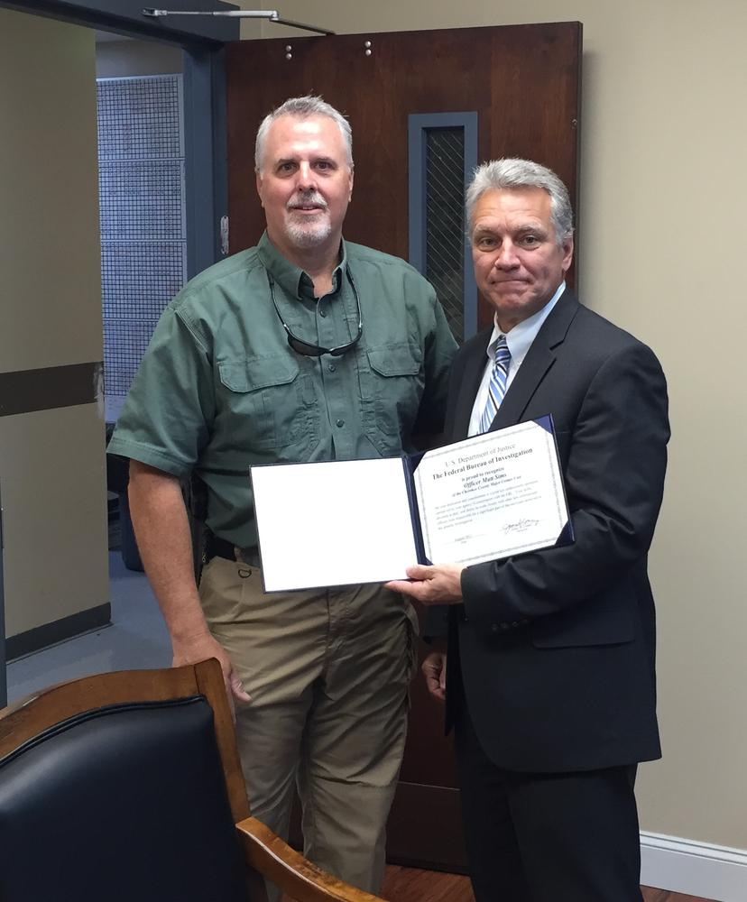 Matt Sims being presented with a certificate of recognition by Bren Tallent of the FBI