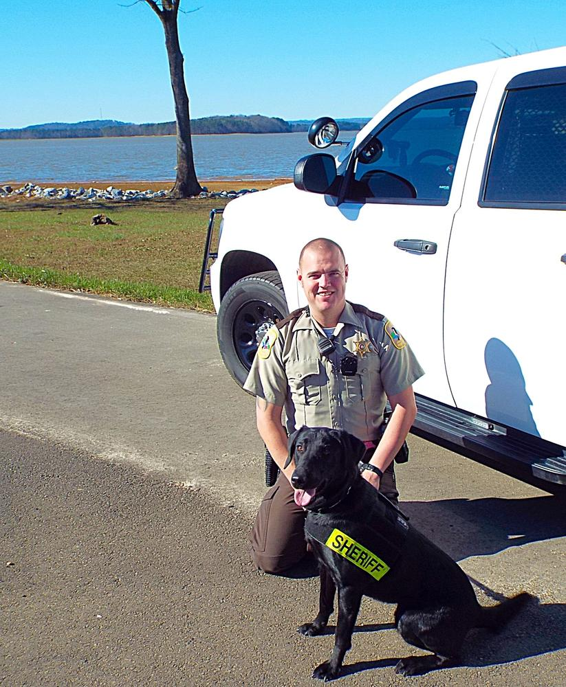 K9 Keelo with handler in front of patrol car
