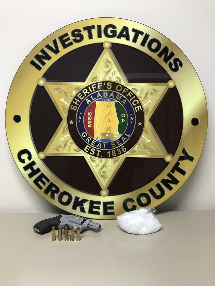 Cherokee County Investigations badge with the handgun and bag of methamphetamine seized during a traffic stop