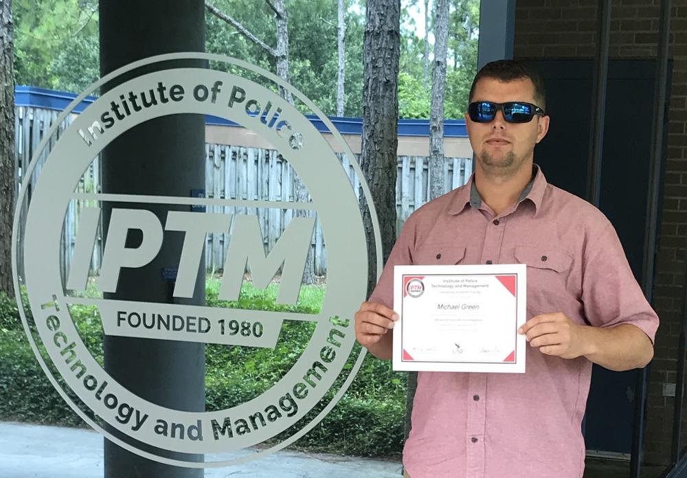 Michael Green holding his certificate from the Institute of Policy Technology and Management