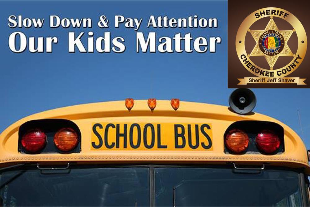 front of a school bus with slow down & pay attention our kids matter in white text and a gold sheriff of cherokee county badge