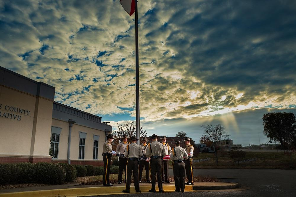 Cherokee County Sheriff's Office Honor Guard standing around the flag pole, preparing to take down the American flag